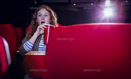 Young woman watching a film and drinking a sodaの写真素材 [FYI00006225]