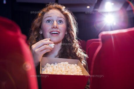 Smiling young woman watching a filmの写真素材 [FYI00006226]