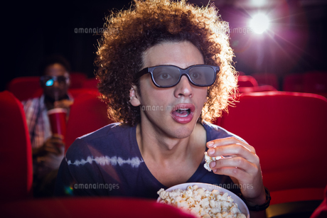 Young man watching a 3d film and eating popcornの写真素材 [FYI00006233]