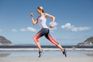 Highlighted leg bones of jogging woman on beachの写真素材 [FYI00006268]