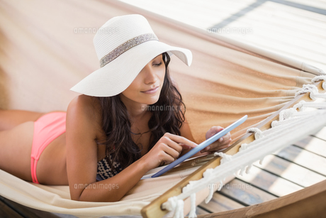 Pretty brunette relaxing on a hammock and using tablet pcの写真素材 [FYI00006300]