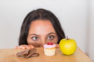 Pretty brunette peeking  at food on tableの写真素材 [FYI00006315]