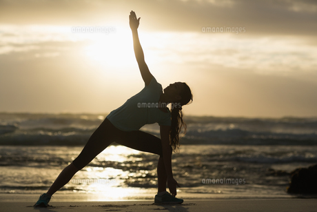Sporty brunette stretching on the beachの素材 [FYI00006332]