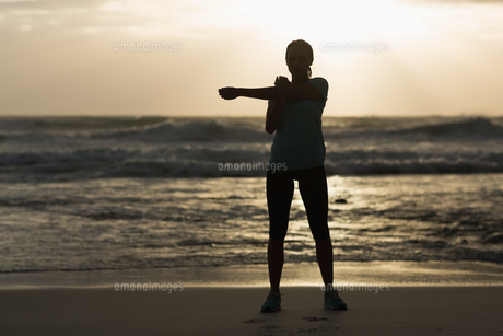 Sporty brunette stretching on the beachの写真素材 [FYI00006333]