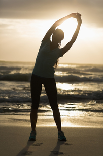 Sporty brunette stretching on the beachの写真素材 [FYI00006334]