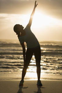 Sporty brunette stretching on the beachの写真素材 [FYI00006335]