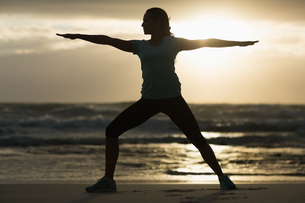 Sporty brunette stretching on the beachの写真素材 [FYI00006337]