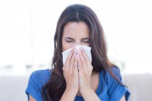 Sick brunette blowing her noseの写真素材 [FYI00006343]
