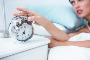 Sleepy young woman in bed extending hand to alarm clockの写真素材 [FYI00006358]