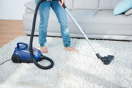 Woman using vacuum cleaner on carpetの写真素材 [FYI00006372]