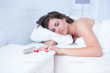 Woman sleeping in bed by spilt bottle of pills on tableの素材 [FYI00006373]