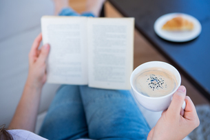 Woman reading book with cup of coffeeの写真素材 [FYI00006374]