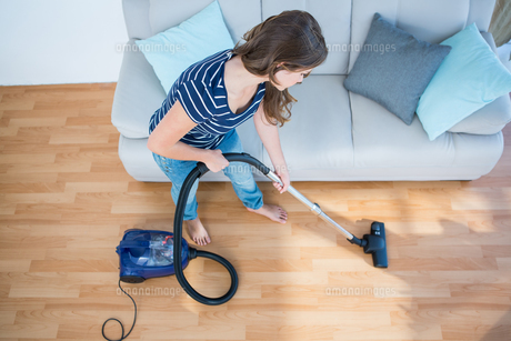 Woman using vacuum cleaner on wooden floorの写真素材 [FYI00006376]
