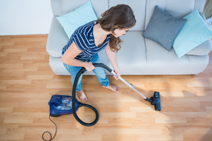 Woman using vacuum cleaner on wooden floorの素材 [FYI00006376]