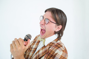 Happy geeky hipster singing with microphoneの写真素材 [FYI00006378]