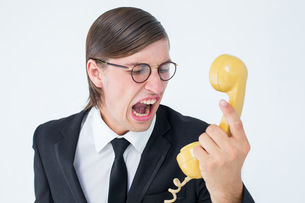 Geeky businessman shouting at retro phoneの写真素材 [FYI00006384]