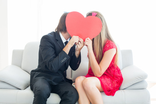 Cute geeky couple kissing and holding heart over facesの写真素材 [FYI00006387]