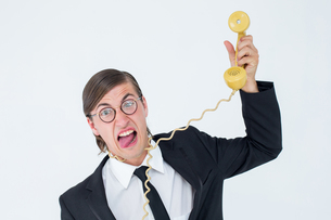 Geeky businessman being strangled by phone cordの写真素材 [FYI00006388]