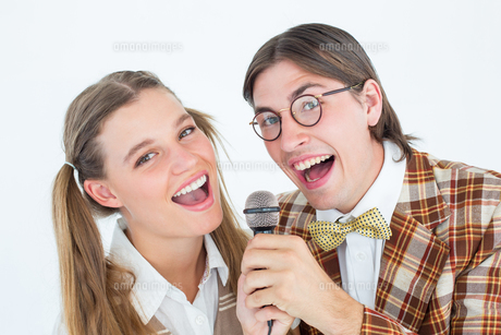 Happy geeky hipsters singing with microphoneの写真素材 [FYI00006389]
