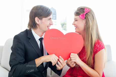 Cute geeky couple smiling and holding heartの写真素材 [FYI00006394]