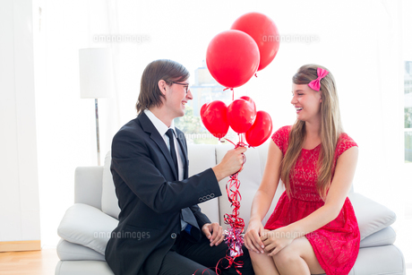 Cute geeky couple with red balloonsの写真素材 [FYI00006395]