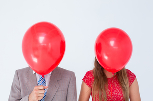 Geeky couple holding balloons in front of their facesの写真素材 [FYI00006401]