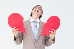 Geeky businessman crying and holding broken heart cardの素材 [FYI00006410]