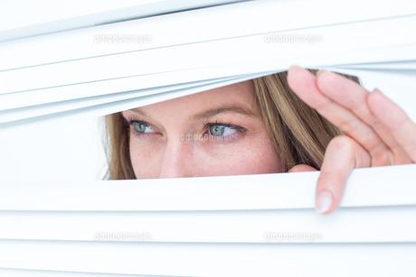 Woman peering through roller blindの素材 [FYI00006438]