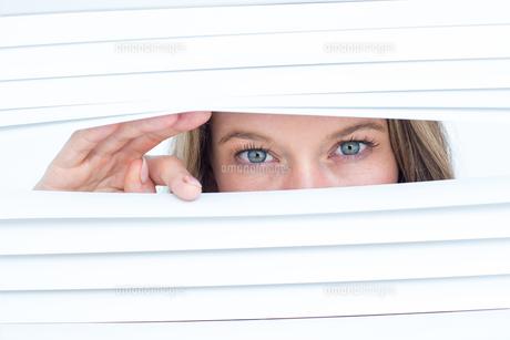 Woman peering through roller blindの素材 [FYI00006444]