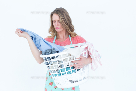 Woman looking at dirty clothesの素材 [FYI00006445]