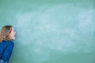 Smiling teacher standing in front of blackboardの写真素材 [FYI00006454]