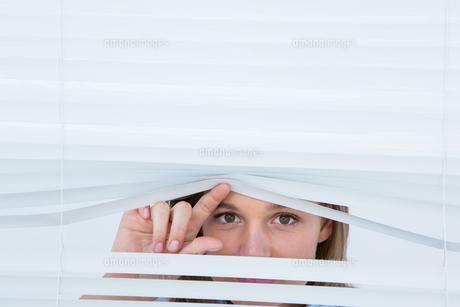Woman peering through roller blindの素材 [FYI00006469]