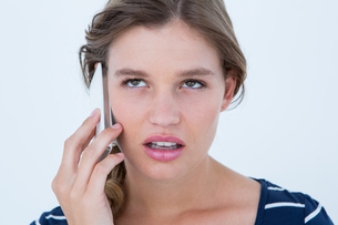 Unsmiling woman calling with her smartphoneの写真素材 [FYI00006471]