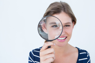 Smiling woman holding magnifying glassの写真素材 [FYI00006475]