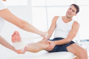 Doctor bandaging her patient ankleの写真素材 [FYI00006491]
