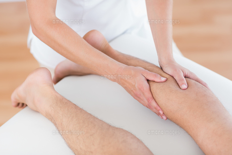 Physiotherapist doing calf massage to her patientの写真素材 [FYI00006492]