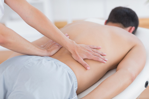 Physiotherapist doing back massage to her patientの写真素材 [FYI00006497]