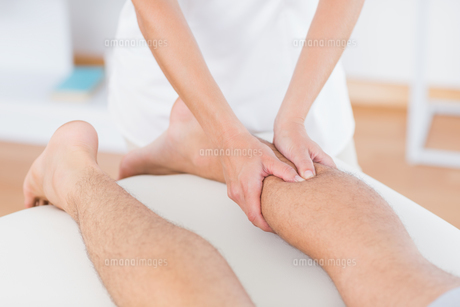 Physiotherapist doing calf massage to her patientの写真素材 [FYI00006500]