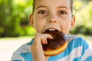 Cute little girl eating doughnutの写真素材 [FYI00006507]