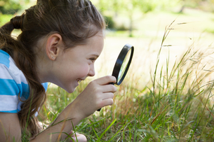 Cute little girl looking through magnifying glassの素材 [FYI00006515]