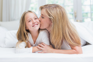 Mother kissing her daughter on the cheek in the bedの写真素材 [FYI00006525]