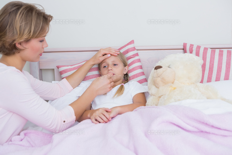 Mother taking the temperature of sick daughterの写真素材 [FYI00006539]