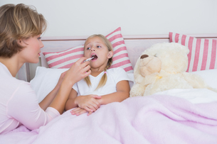 Mother taking the temperature of sick daughterの写真素材 [FYI00006540]