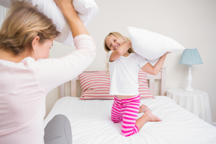 Mother and daughter having pillow fightの写真素材 [FYI00006551]