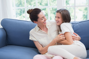 Mother and daughter laughing on couchの写真素材 [FYI00006584]