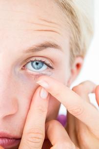 Pretty blonde applying contact lensの写真素材 [FYI00006614]
