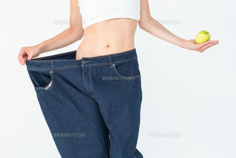 Slim woman wearing too big jeans holding an appleの素材 [FYI00006619]