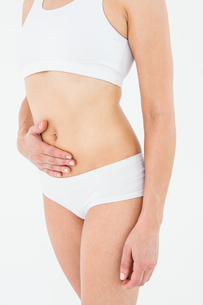 Fit woman suffering from stomach painの写真素材 [FYI00006640]