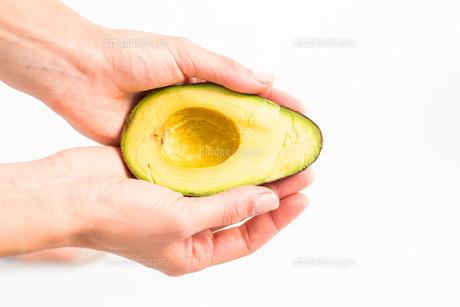 Woman presenting half of an avocadoの写真素材 [FYI00006646]
