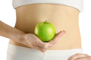 Slim woman holding green appleの素材 [FYI00006677]